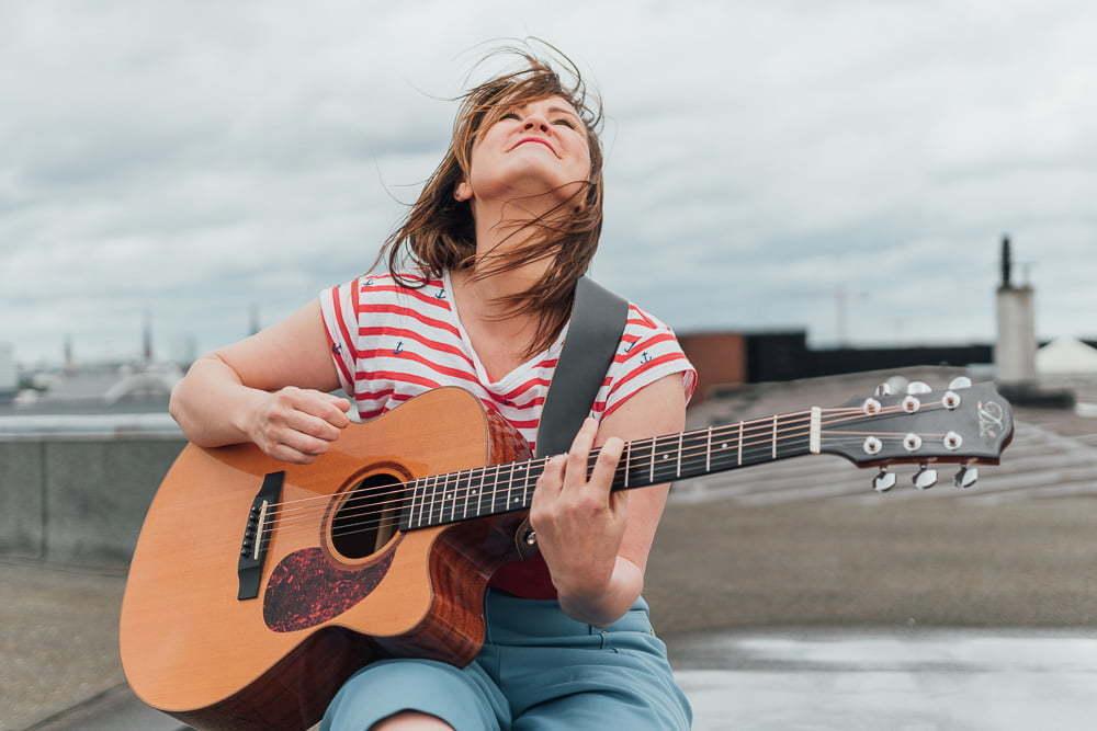 Frau mit Gitarre in der Hand beim Fotoshooting