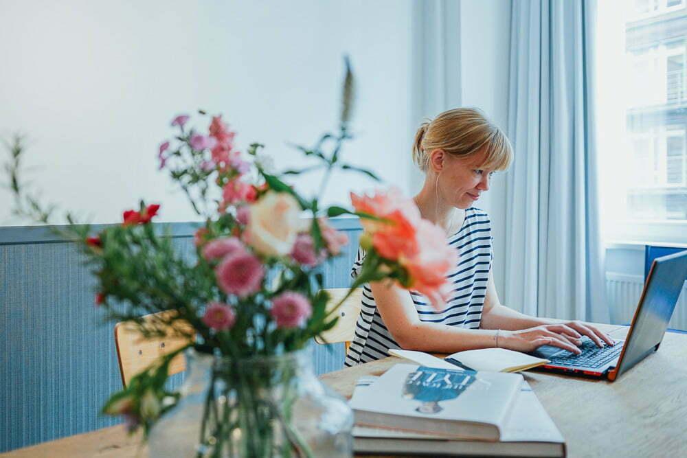 Frau sitzt beim Personal Brand Fotoshooting am Tisch mit einem Laptop