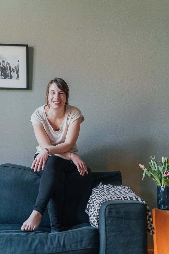Frau sitzt bei einem Fotoshooting auf der Lehne des Sofas