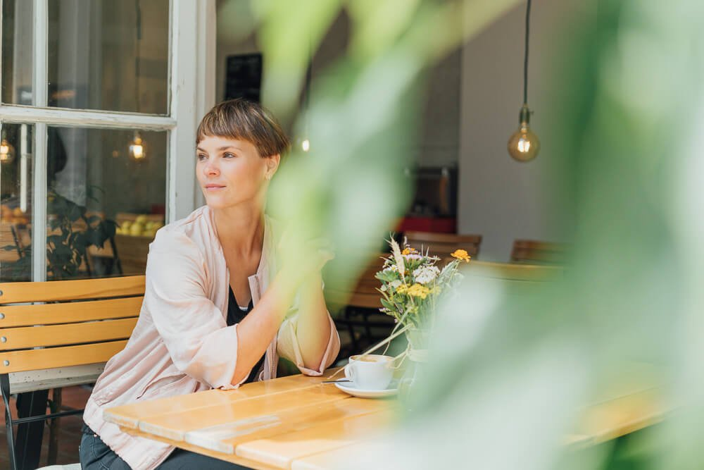 Personal Branding Frau sitz am Fenster im Parkcafe
