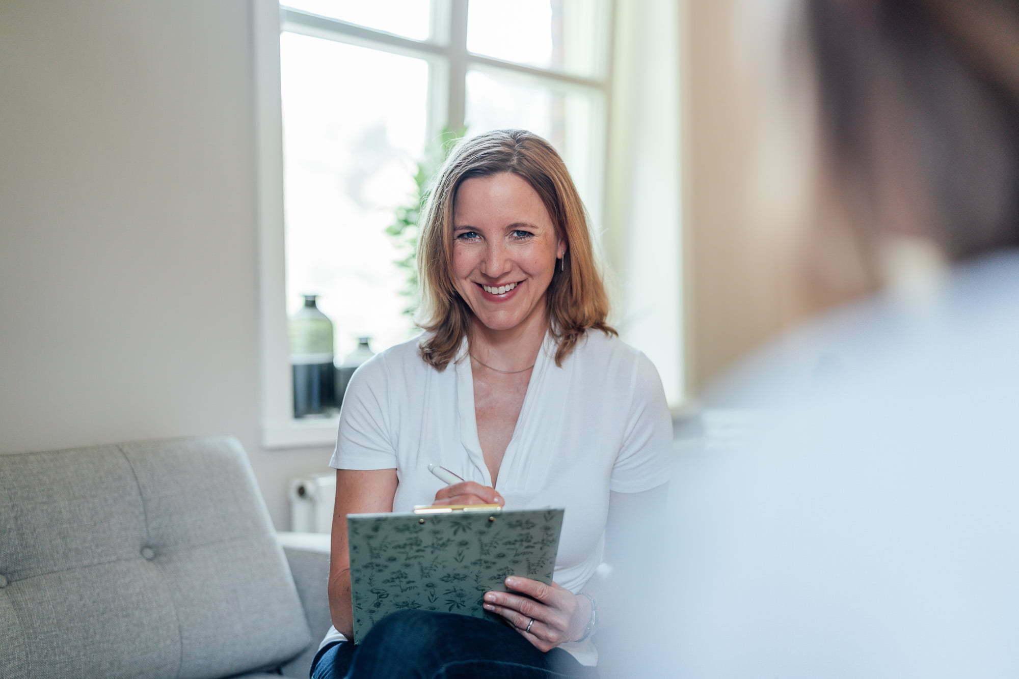 Frau sitzt mit Klemmbrett auf dem Sofa und schaut in die Kamera
