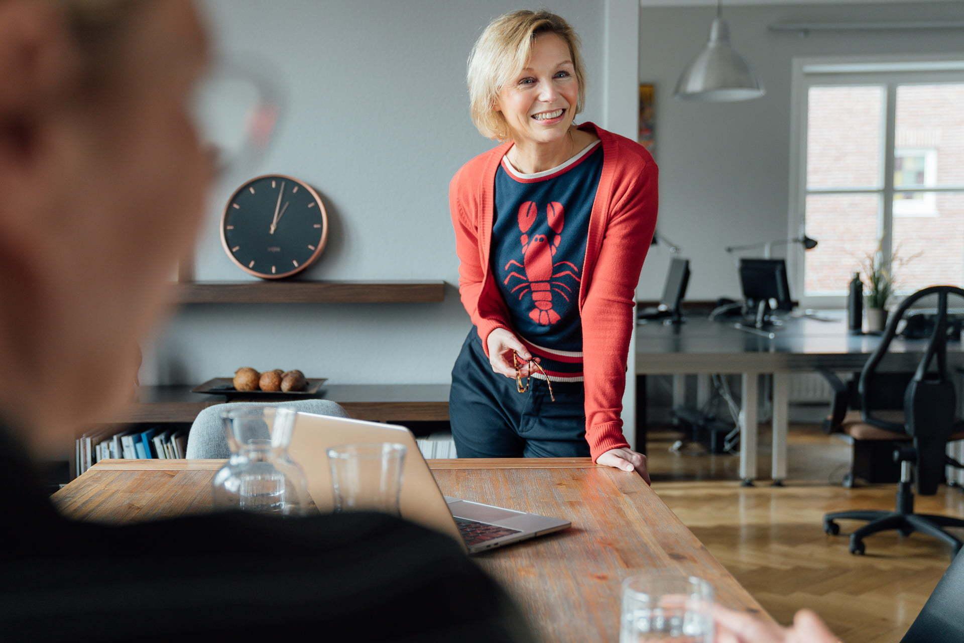 Frau an den Tisch lehnend während eines Fotoshootings