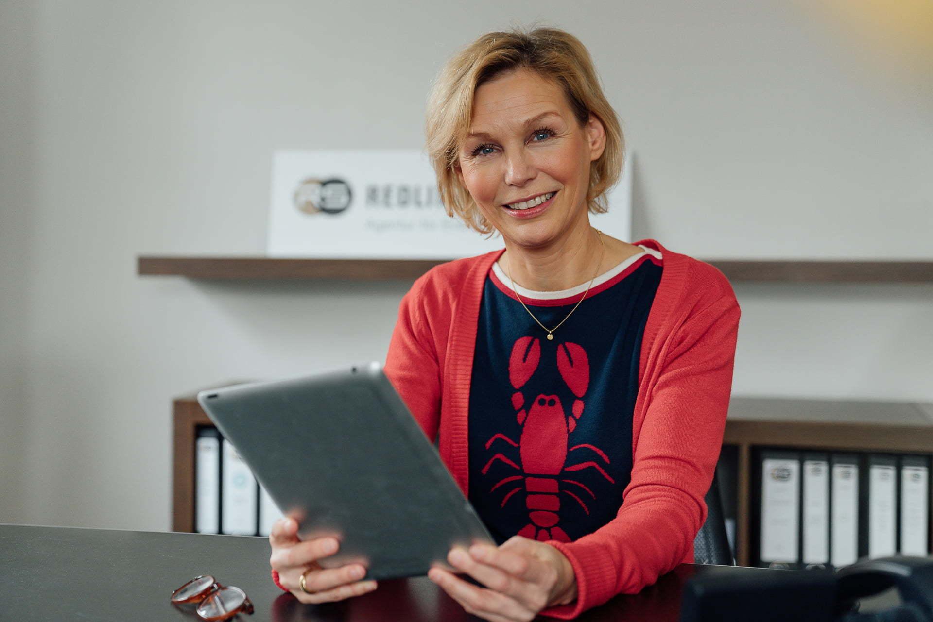 Frau sitzt am Schreibtisch mit einem Tablet während eines Personal Branding Fotoshootings