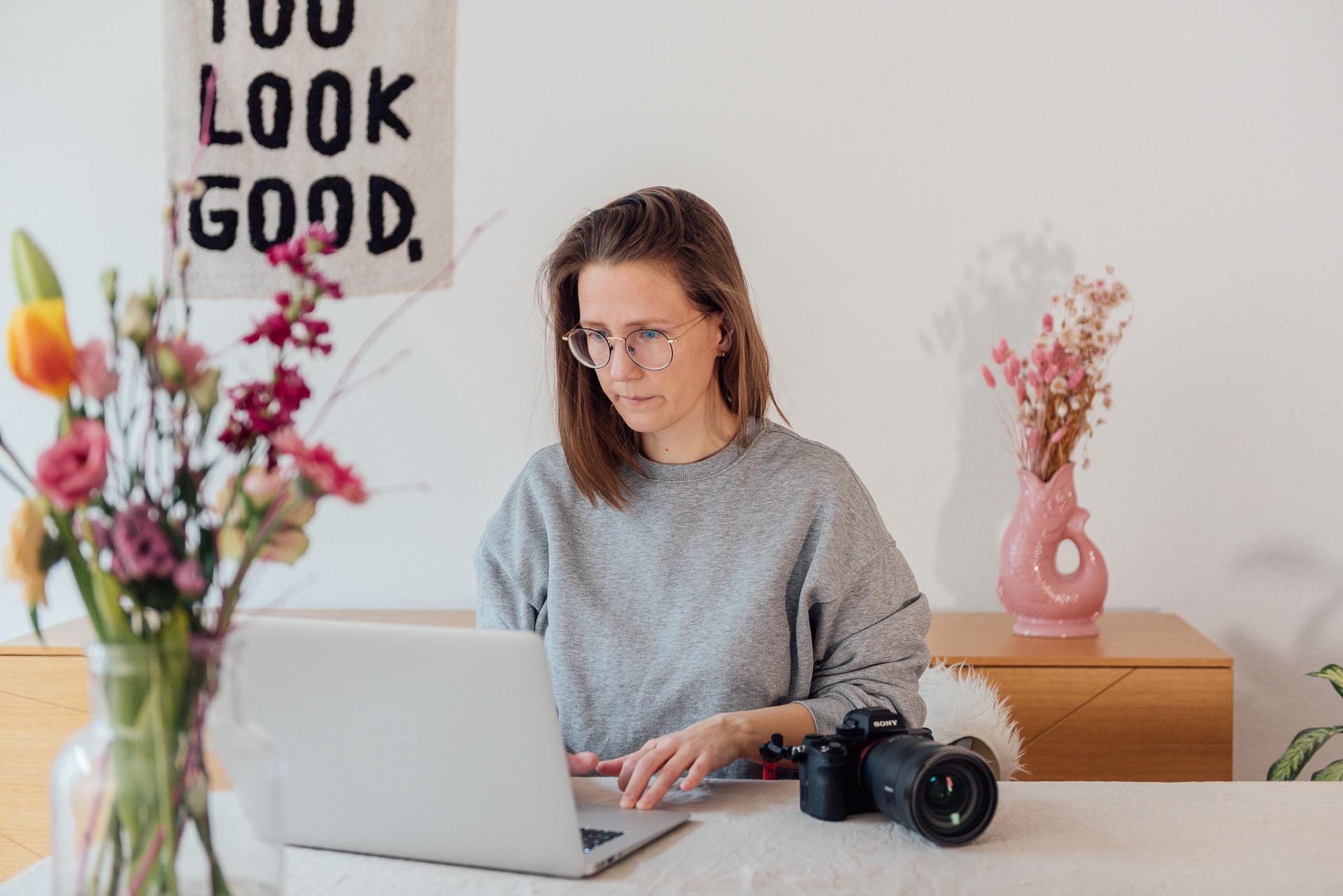 Fotografin Mirjam Kilter sitzt mit ihrer Kamera am Tisch an einem Macbook