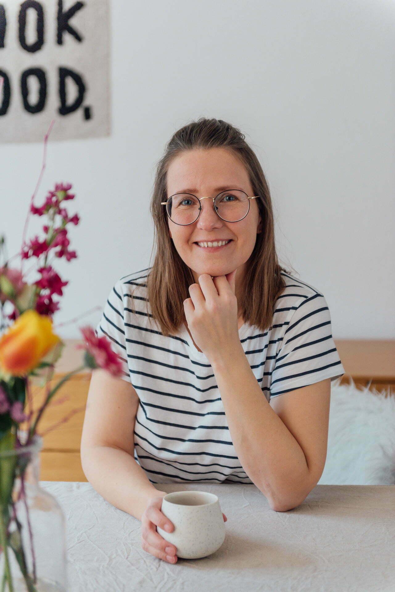 Die Personal Branding Fotografin Mirjam Kilter sitzt mit einer Tasse Kaffee an einem Tisch