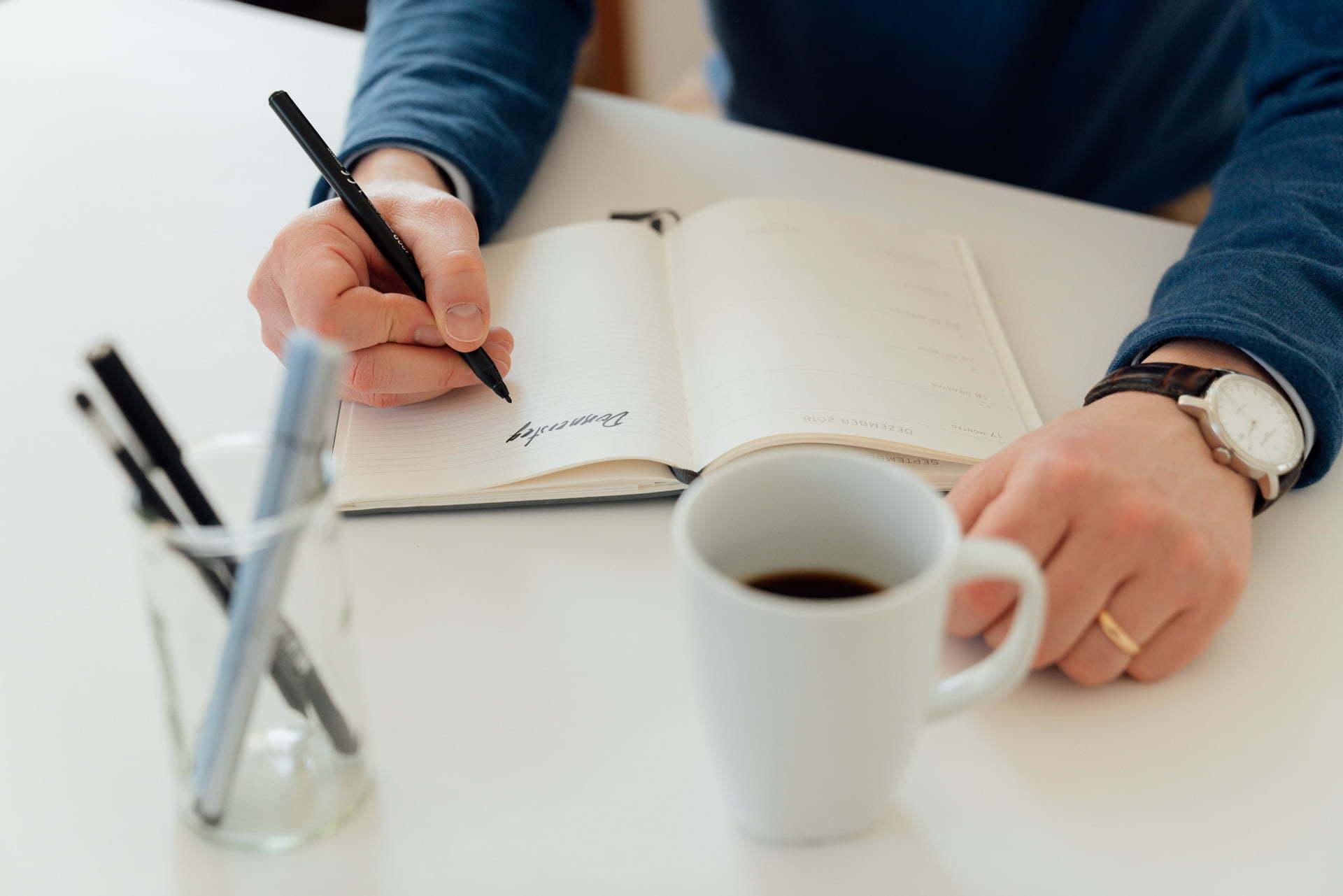 Detailaufnahme von Händen die in ein Notizbuch schreiben