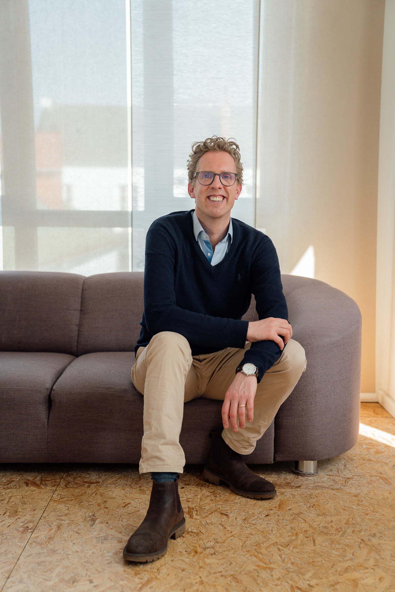 Timon Kühne sitzt auf dem Sofa während eines Fotoshootings