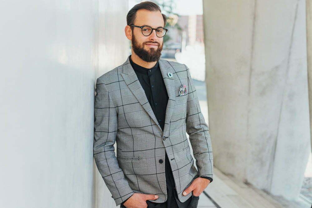 Mann im Anzug lehnt während eines Businessshootings an einer Wand