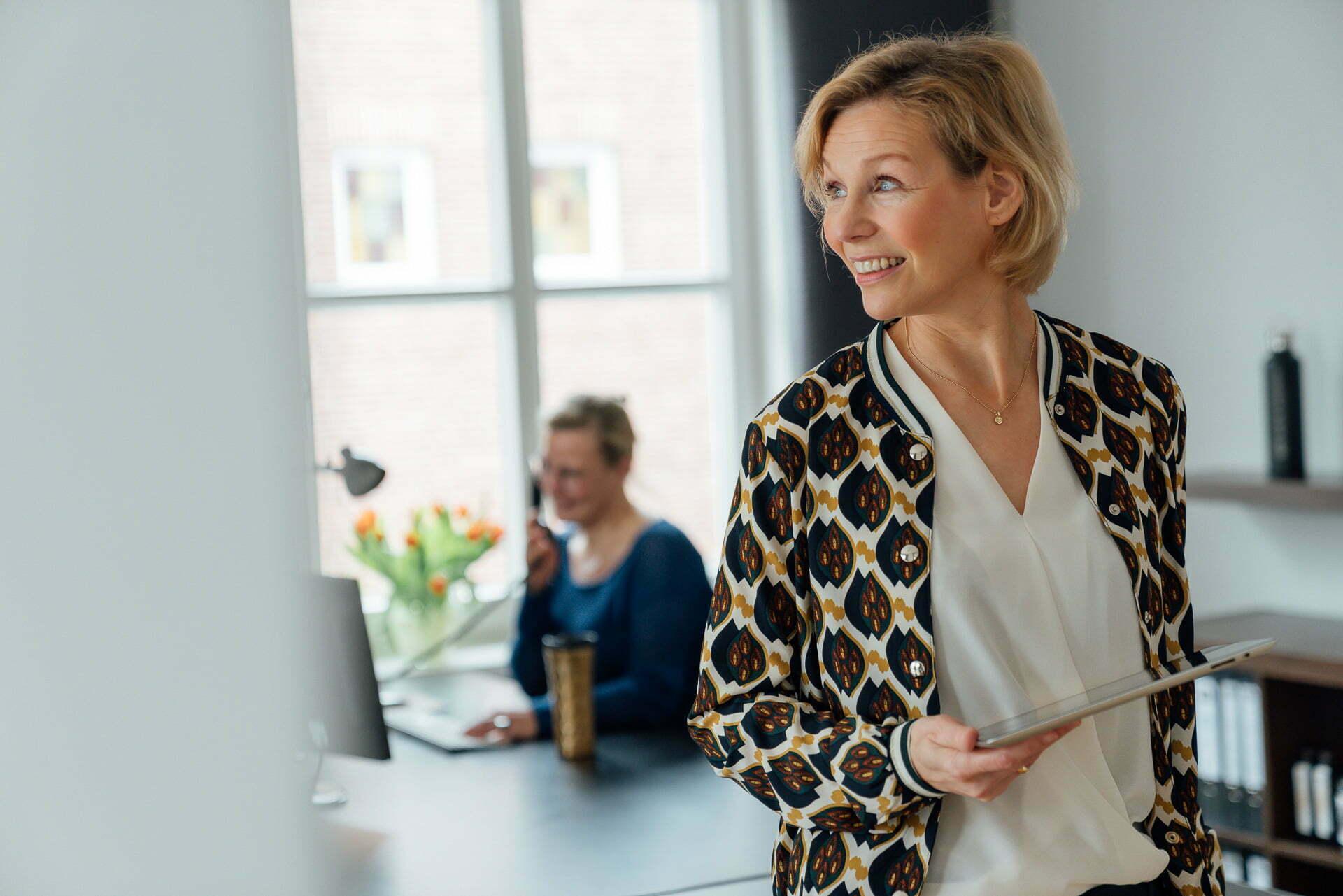 Frau steht mit einem Tablet in der Hand vor einem Schreibtisch